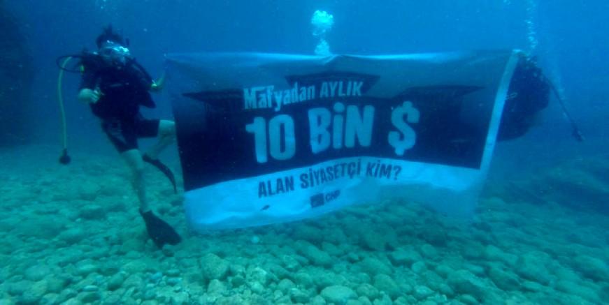 Denizin  altında '128 milyar dolar nerede?' ve '10 bin dolar alan kim?' pankartı